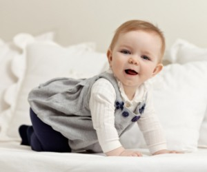 little girl walking all fours on bed