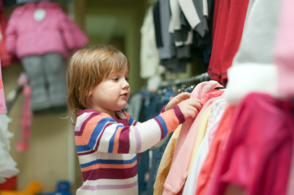 2 years  girl  chooses dress at  shop